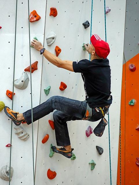 Man with a red hat on a climbing wall