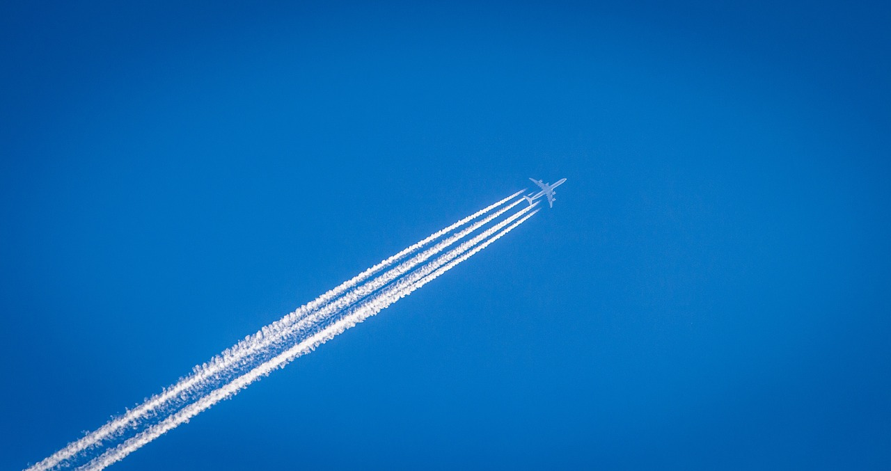 Aircraft in sky with lines behind