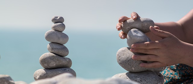 Balancing rocks and bundle of rocks in hands by the sea