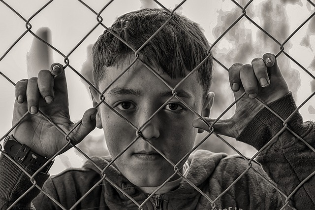 Black and white photo of a child behind a wire link fence