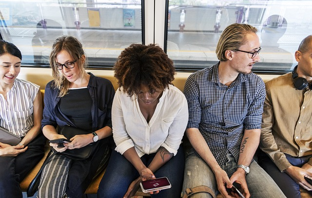 Diverse commuters on a train looking at devices