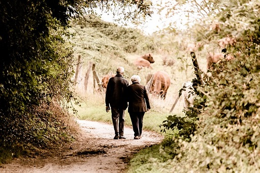 old couple walking in the woods