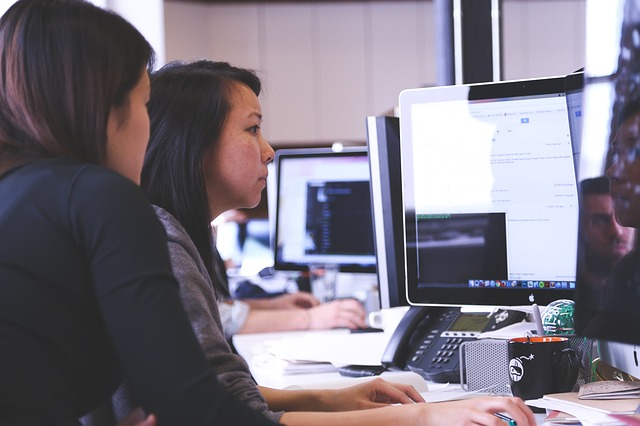 Two women in an office looking at one desktop monitor