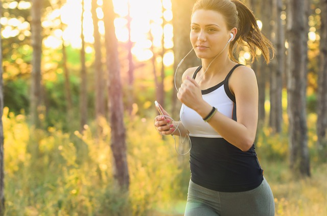 Woman running in the woods with earphones